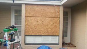 window being boarded up and repaired
