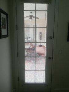 tempered glass patio door with grids and broken glass